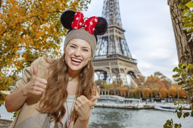 tourist woman wearing Minnie Mouse Ears showing thumbs up, Paris