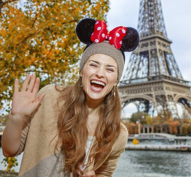tourist woman in Minnie Mouse Ears in Paris handwaving