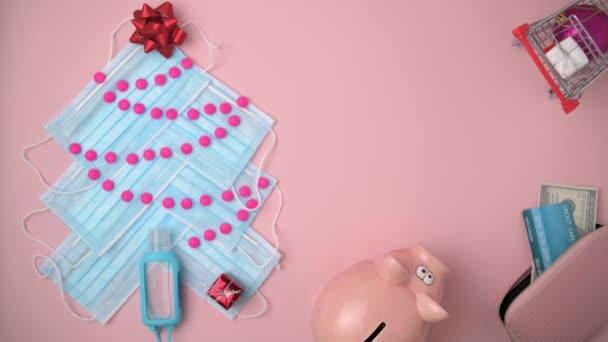 Veselé Vánoce. byt ležel s prasečí bankou, nákupní košík, peněženka, kreditní karta, dárcovská dárková krabice, vánoční stromeček z lékařských masek, pilulky a dezinfekční prostředky na růžovém pozadí. Kodek PRORes 422.