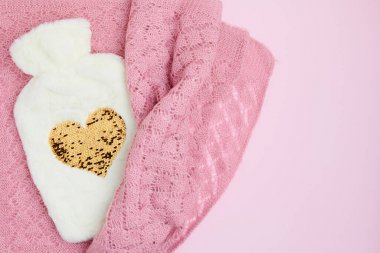 winter flat lay with hot water warmer on pink background.