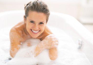 Happy young woman sitting in bathtub