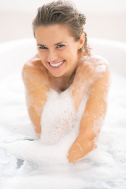 Happy young woman sitting in bathtub
