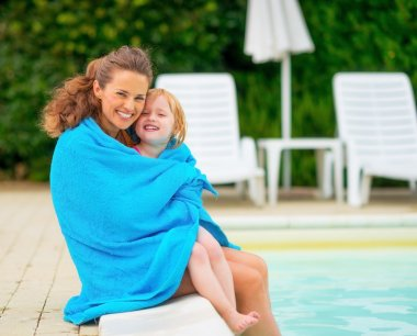 Portrait of happy mother and baby girl wrapped in towel sitting