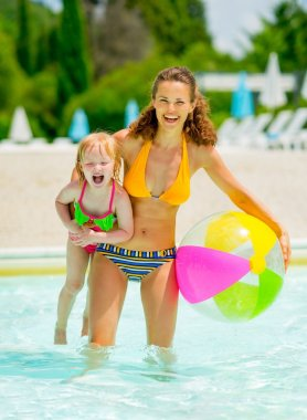 Portrait of happy mother and baby girl with ball in swimming poo