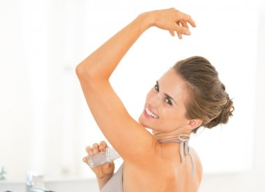 Portrait of happy young woman applying deodorant on underarm