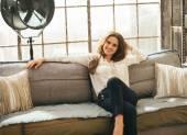 Entspannte junge Frau sitzt auf Couch in Dachgeschosswohnung