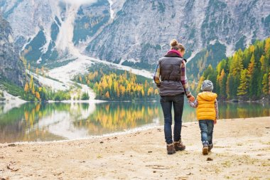 Mother and baby walking on lake braies in south tyrol, italy. re