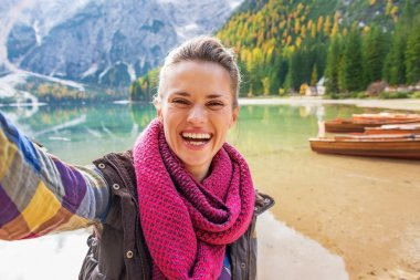 Happy young woman making selfie on lake braies in south tyrol, i
