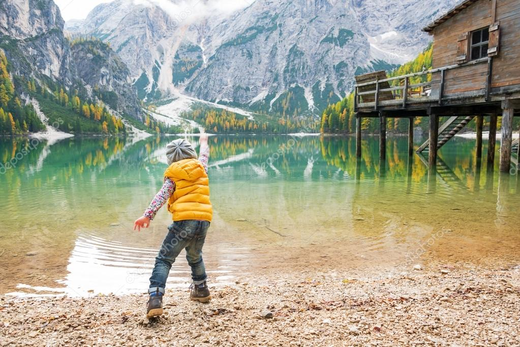 Child throwing stones on lake braies in south tyrol, italy. rear