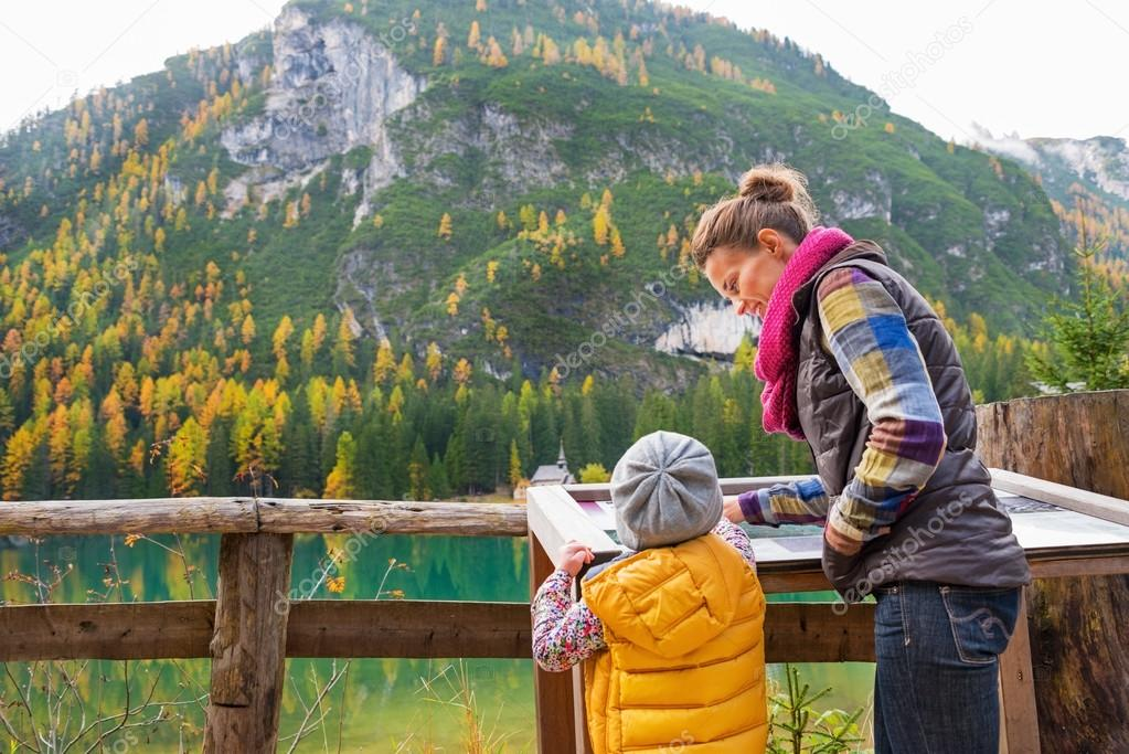 Mother and baby looking in information board while on lake braie