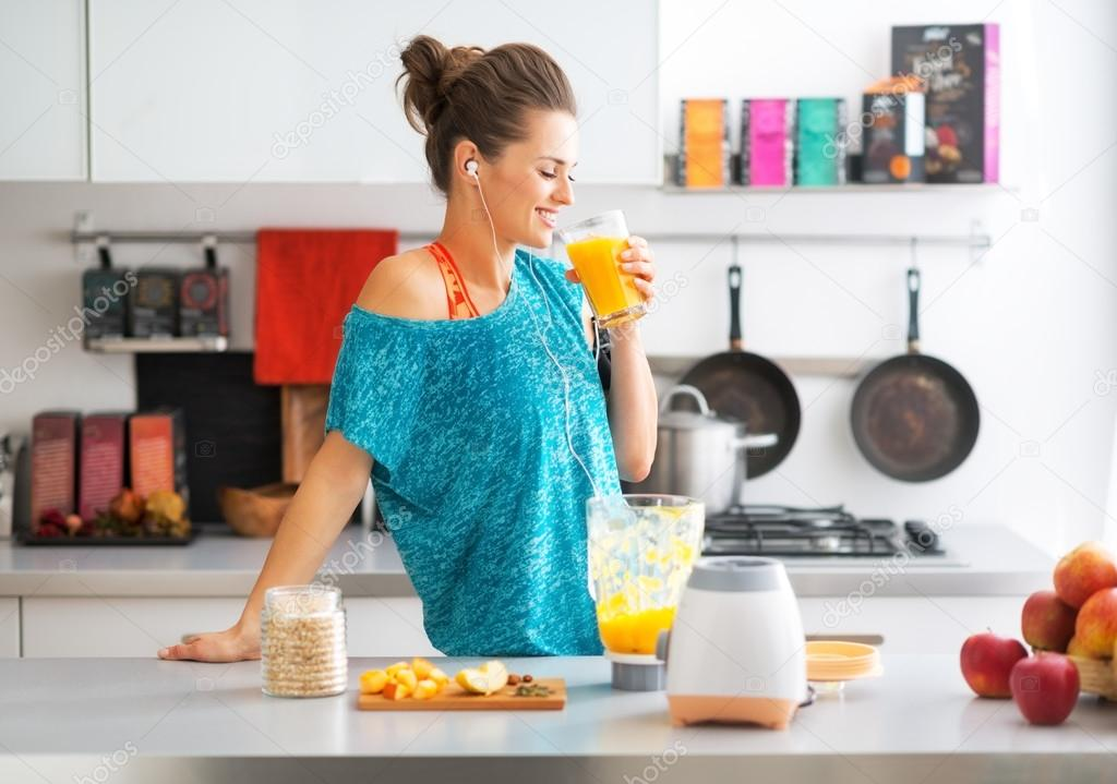 Happy fitness young woman drinking pumpkin smoothie in kitchen