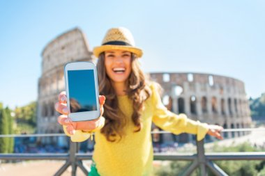 Closeup on happy young woman showing cell phone in front of colo