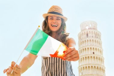 Happy young woman showing italian flag in front of leaning tower
