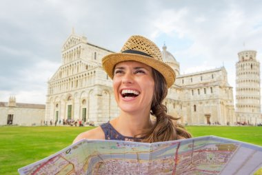 Smiling young woman with map on piazza dei miracoli, pisa, tusca