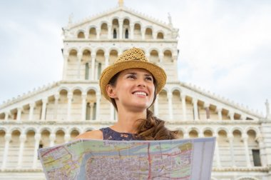 Happy young woman with map in front of duomo di pisa, pisa, tusc