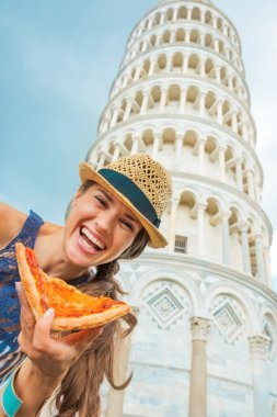 Happy young woman with pizza in front of leaning tower of pisa,