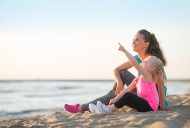 Healthy mother and baby girl pointing while sitting on beach in