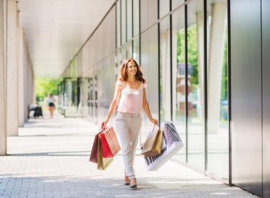 Brown-haired woman walking in sunlight on a shopping spree