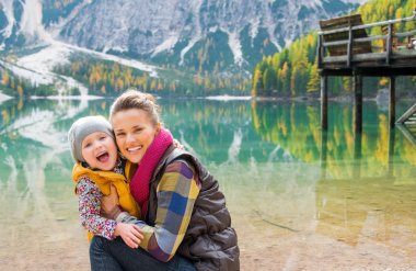 Mother and daughter laughing cheek to cheek on Lake Bries