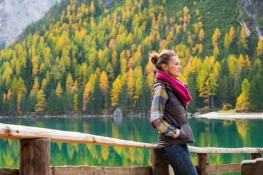 Woman hiker with hands in pockets rests at Lake Bries