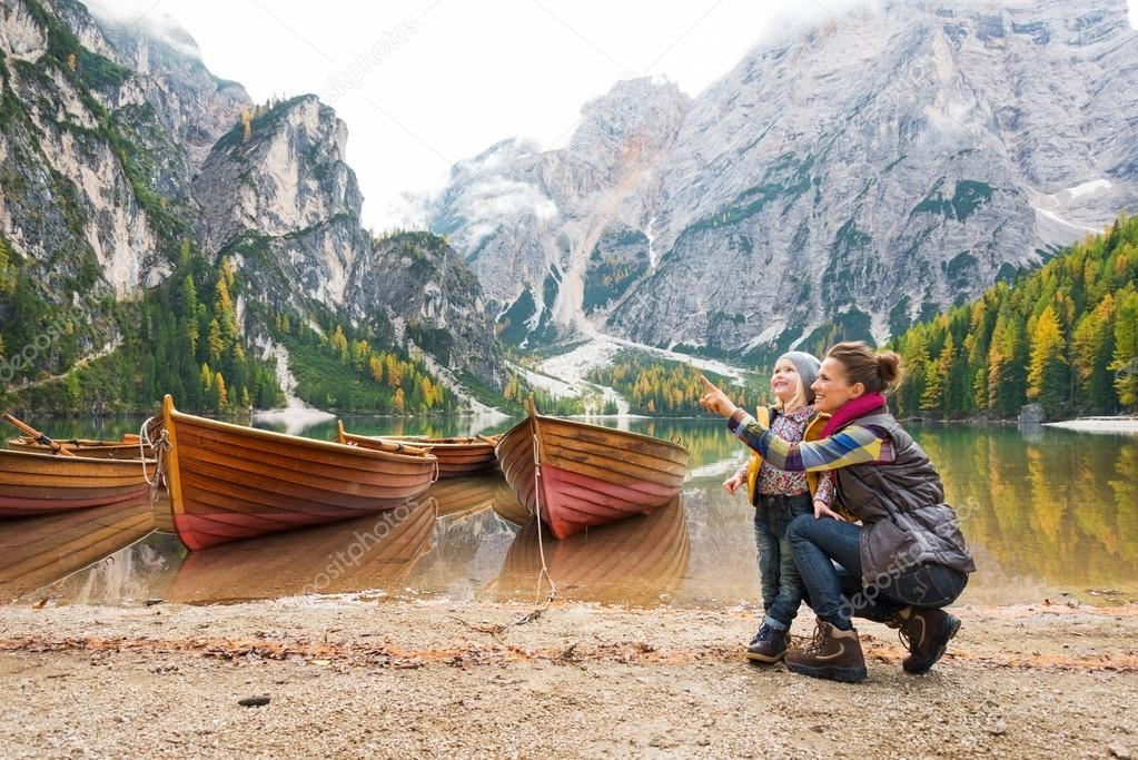 Mother pointing at scenery with daughter on shores of Lake Bries