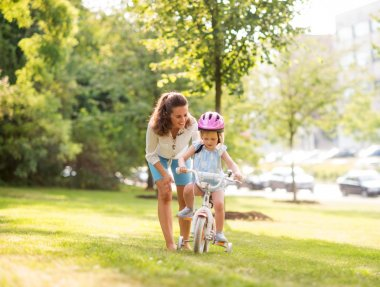 Mother teaching her daughter how to ride a bicycle in a park