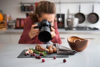 A woman food photographer in the background leans down to take a close-up, in a modern kitchen, of autumn fruits and vegetables - mushrooms, garlic, rosemary, and cranberries. stock vector