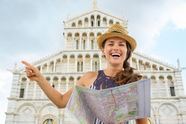 Smiling woman tourist holding map and pointing in Pisa