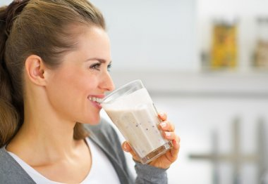 Profile portrait of happy young woman drinking fresh smoothie