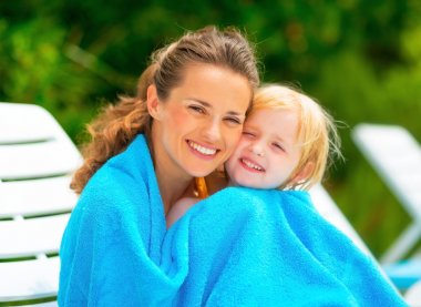 Portrait of smiling mother and baby girl wrapped in towel sittin