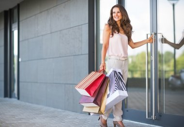 Full length portrait of happy young woman with shopping bag