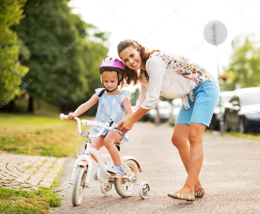 Mother helping baby girl riding bicycle