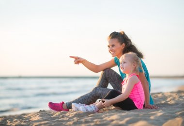 Pointing mother with daughter in workout gear sitting on beach