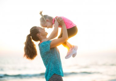 Happy mother holding child up in air at the beach at sunset