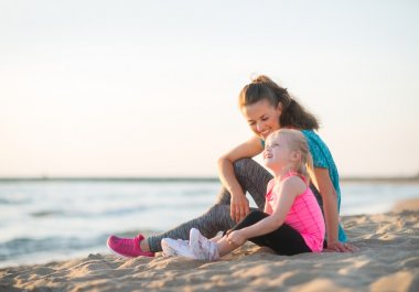 Happy young mother and daughter talking and sitting on the beach