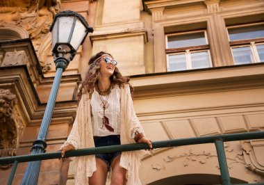 smiling boho chic with sunglasses near old town streetlight