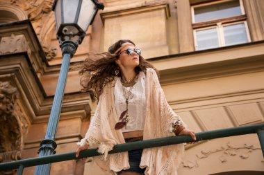 Longhaired bohemian girl with sunglasses near old town streetlig