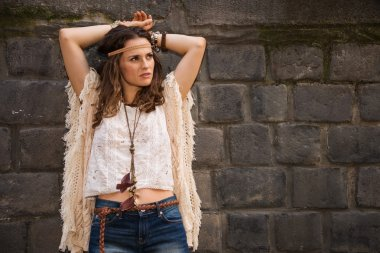 portrait of relaxed boho young woman near stone wall