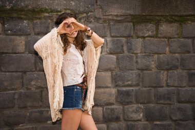 Longhaired hippy young woman near stone wall making heart hand
