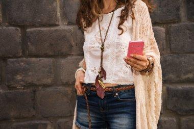 closeup on boho young woman near stone wall writing sms