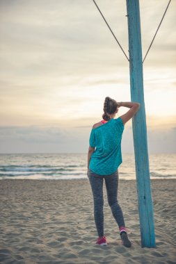 Woman seen from behind in fitness gear watching sunset on beach
