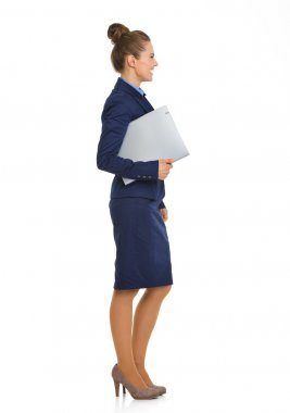 Smiling businesswoman in suit standing in profile holding file