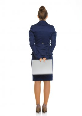 Businesswoman seen from behind holding file behind her