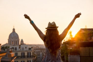 Woman from behind with outstretched arms in Rome at sunset
