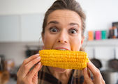 Fényképek Teasing, happy woman taking big bite of corn on the cob