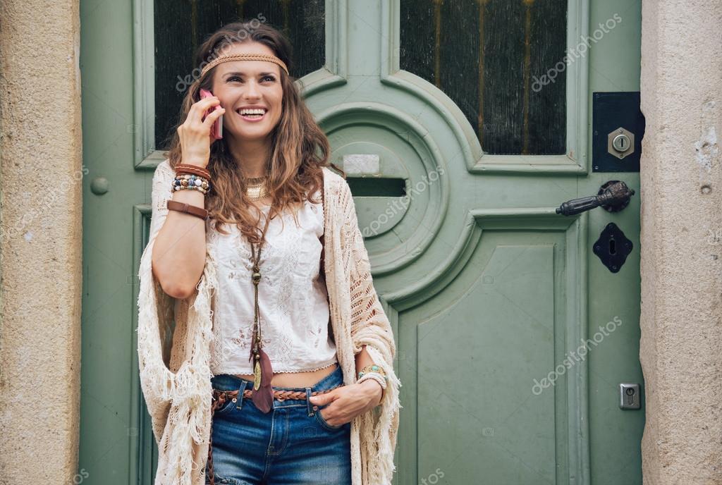 1a975dc7a8b81 Rire de femme brunette hippie chez femme vêtements Bohème adossé à  l extérieur de la porte en bois dans la vieille ville et en parlant de  téléphone ...