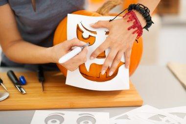 Woman using stencils to carve pumpkin Jack-O-Lantern. Closeup