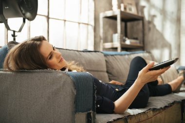 Relaxed woman lying on sofa and watching tv in loft apartment