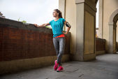 Fotografie Young fitness woman is getting ready for outdoors jogging