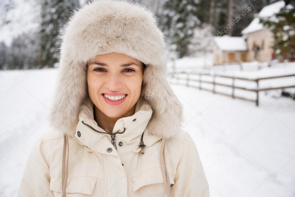 Portrait of happy young woman in furry hat in winter outdoors